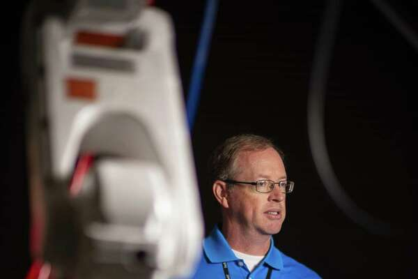 """Bill Rafferty,a regional director for the Texas Manufacturing Assistance Center,stands next to a collaborative robot at their facilities on Friday, September 7, 2018. The Southwest Research Institute recently announced the opening of a collaborative robotics lab designed to help manufacturers figure out how robots and humans can work together. The so-called """"cobots"""" can safely perform tasks alongside humans."""