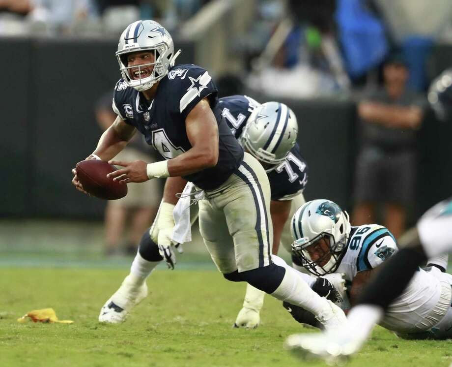 Dallas Cowboys' Dak Prescott (4) is sacked by Carolina Panthers' Wes Horton (96) during the second half of an NFL football game in Charlotte, N.C. It's no secret that Prescott and his revamped group of Dallas receivers hold the key to creating consistent running room for Ezekiel Elliott. The formula needs improvement with the Cowboys trying to avoid their first 0-2 start under Jason Garrett. Photo: Jason E. Miczek /Associated Press / Copyright 2018 The Associated Press. All rights reserved