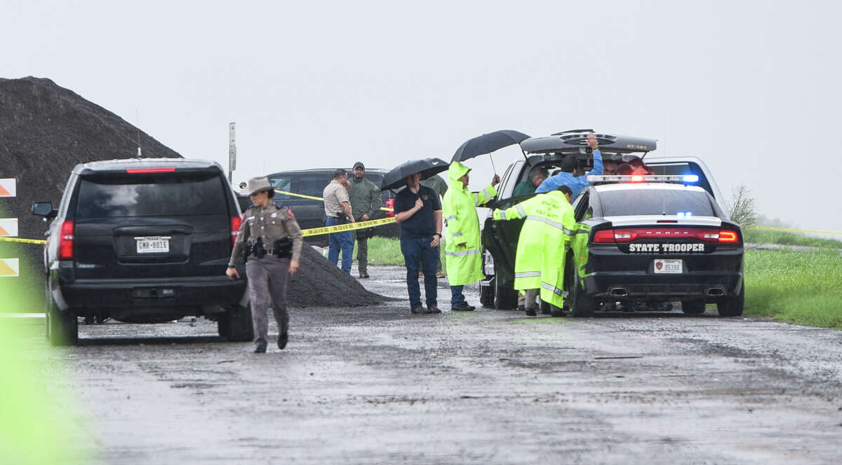 Law enforcement investigates the scene where a fourth body was found was found Saturday, Sept. 15, 2018, near mile marker 14 of Interstate 35. A Border Patrol agent has been detained in connection with the slaying of four prostitutes.