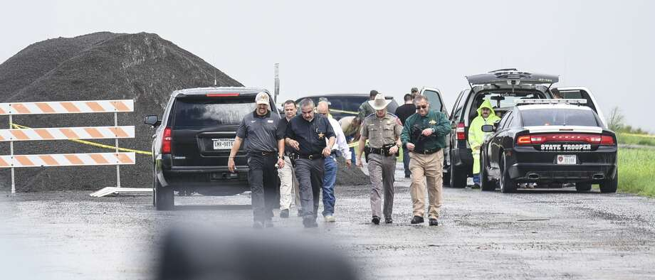 "Webb County District Attorney Isidro ""Chilo"" Alaniz and Webb County Sheriff Martin Cuellar, along with other law enforcement officials, walk away from the scene where a fourth body was found Saturday, Sept. 15, 2018, near mile marker 14 of Interstate 35. A Border Patrol agent has been detained in connection with the slaying of four prostitutes. Photo: Danny Zaragoza/Laredo Morning Times"