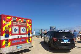 Emergency personnel respond to Newcomb Hollow Beach in Wellfleet, Mass, on Saturday, Sept. 15, 2018. The Cape Cod Times says rescue crews responded to Newcomb Hollow Beach in Wellfleet at around noon Saturday after one person was apparently bitten by a shark. It�s not immediately clear the extent of the person�s injuries. (Eric Williams/The Cape Cod Times via AP)
