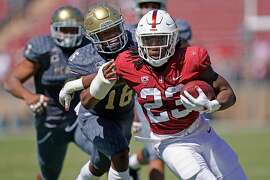 Stanford Cardinal running back Trevor Speights (23) runs for a gain against UC Davis Aggies defensive back Erron Duncan (16) during the first half of an NCAA football game at Stanford Stadium, Saturday, Sept. 15, 2018, in Stanford, Calif.