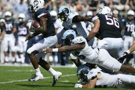 UConn quarterback David Pindell, left, pulls away from Rhode Island defensive lineman Keith Wells, top, and linebacker Justin Hogan on Saturday.