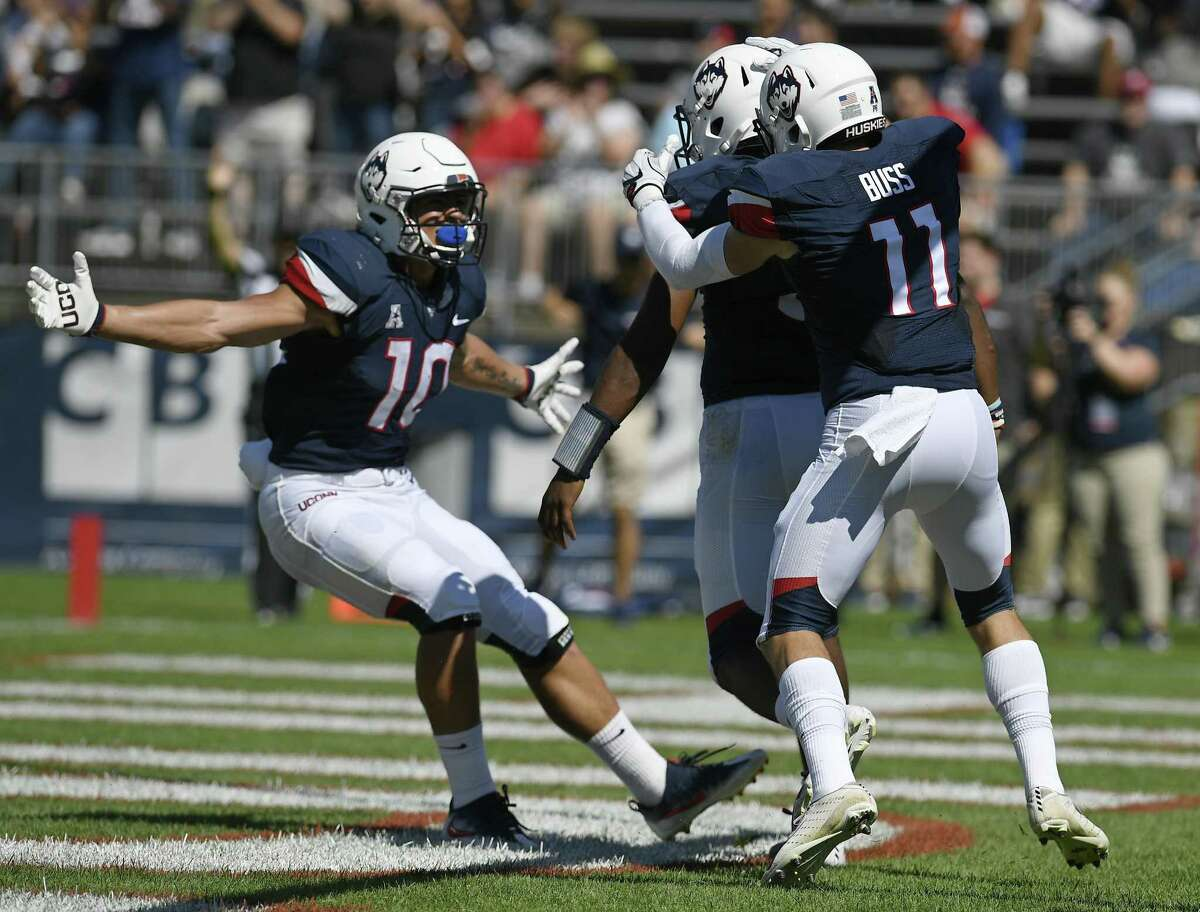 UConn quarterback David Pindell, center, celebrates his touchdown with teammates running back Zavier Scott (10), and wide receiver Kyle Buss (11) on Saturday.