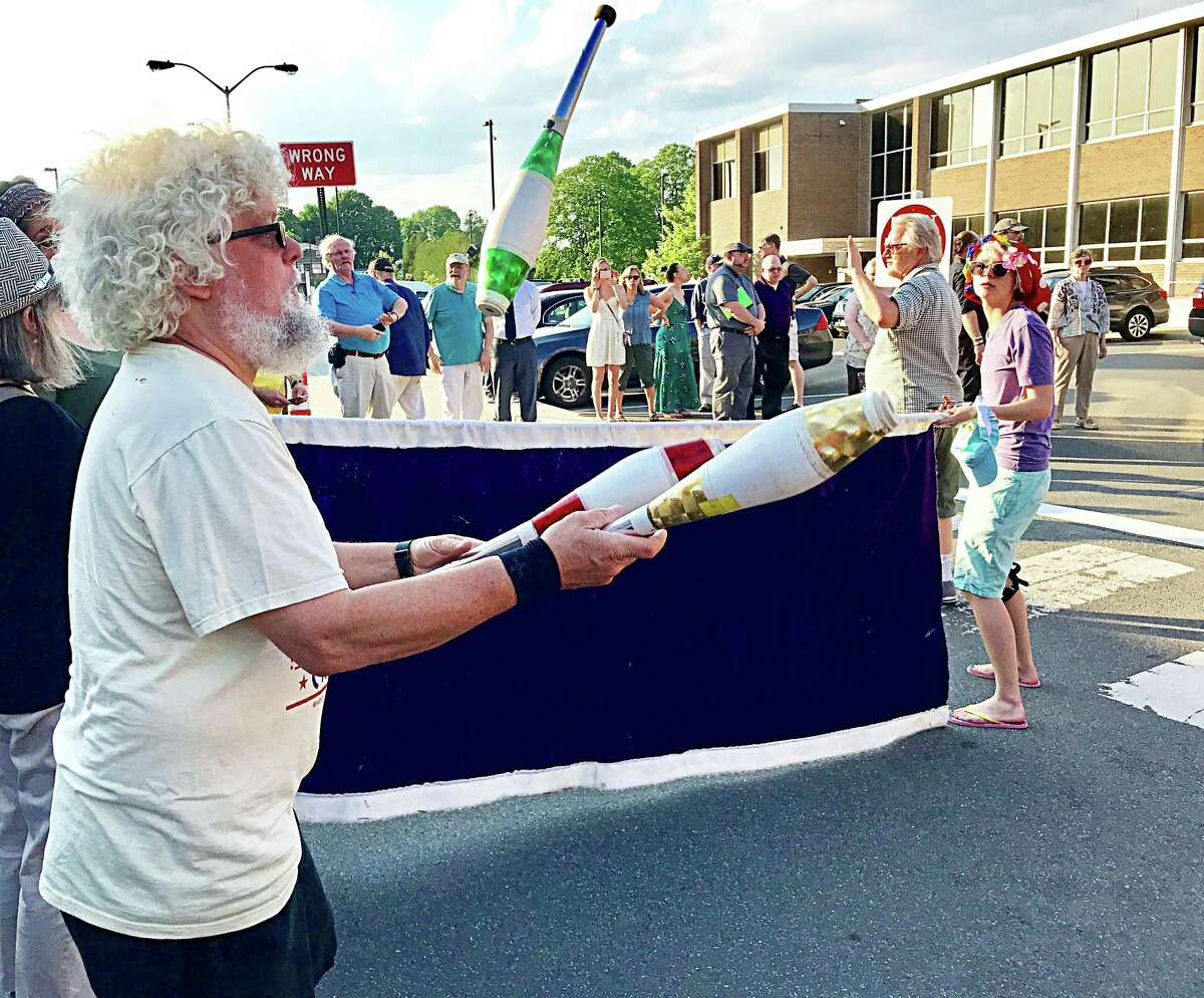 Executive Director of Oddfellows Playhouse Dic Wheeler juggles as part of a protest outside City Hall in May. Participants opposed cuts to the arts & culture coordinator's salary, which was reinstated that evening.