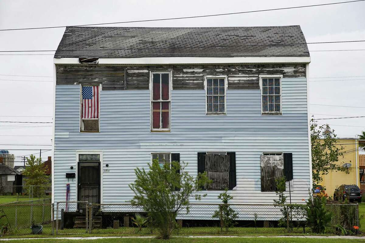 An American flag hangs in a window of a boarded up home Thursday Sept. 13, 2018 in Galveston ten years after Hurricane Ike hit the Texas coast.