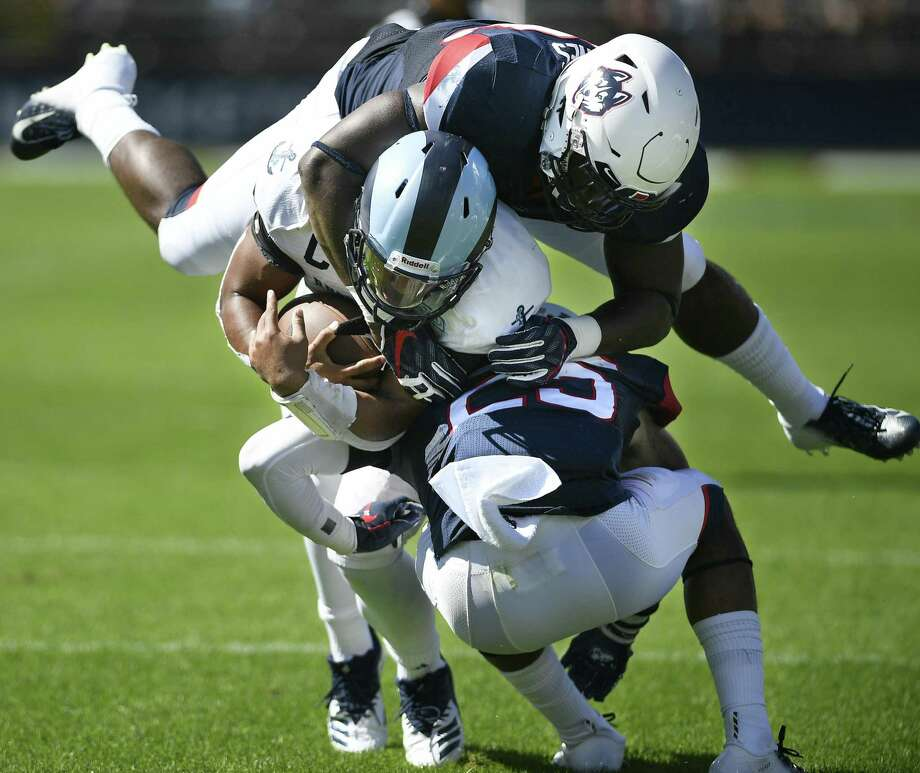 Rhode Island quarterback JaJuan Lawson (15) is sandwiched in a tackle by UConn linebacker Kevon Jones, top, and defensive back Tyler Coyle in Saturday's game. Photo: Jessica Hill / Associated Press / Copyright 2018. The Associated Press. All rights reserved.