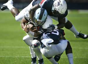 Rhode Island quarterback JaJuan Lawson (15) is sandwiched in a tackle by UConn linebacker Kevon Jones, top, and defensive back Tyler Coyle in Saturday's game.