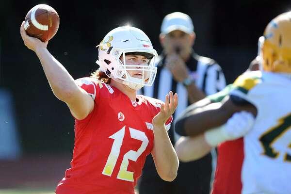 Greenwich quarterback Gavin Muir throws a pass against Trinity Catholic on Saturday.