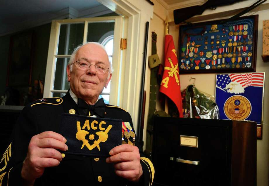 Retired Army Staff Sergeant Eric Muth poses with an Army Chemical Corps arm band at his home in Milford, Conn., on Friday Aug. 31, 2018. Muth was a volunteer for the special banch during the Cold War era. Muth recently donated a trove of documents and other related material to the army's military museum. Photo: Christian Abraham / Hearst Connecticut Media / Connecticut Post