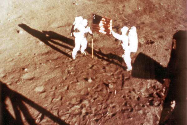 "In this NASA handout file photo taken on July 20, 1969, U.S. astronauts Neil Armstrong and ""Buzz"" Aldrin deploy the U.S. flag on the lunar surface during the Apollo 11 lunar landing mission."