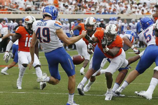 Oklahoma State linebacker Amen Ogbongbemiga (11) blocks a punt by Boise State punter Quinn Skillin (49) in the first alf of an NCAA college football game in Stillwater, Okla., Saturday, Sept. 15, 2018. (AP Photo/Sue Ogrocki)
