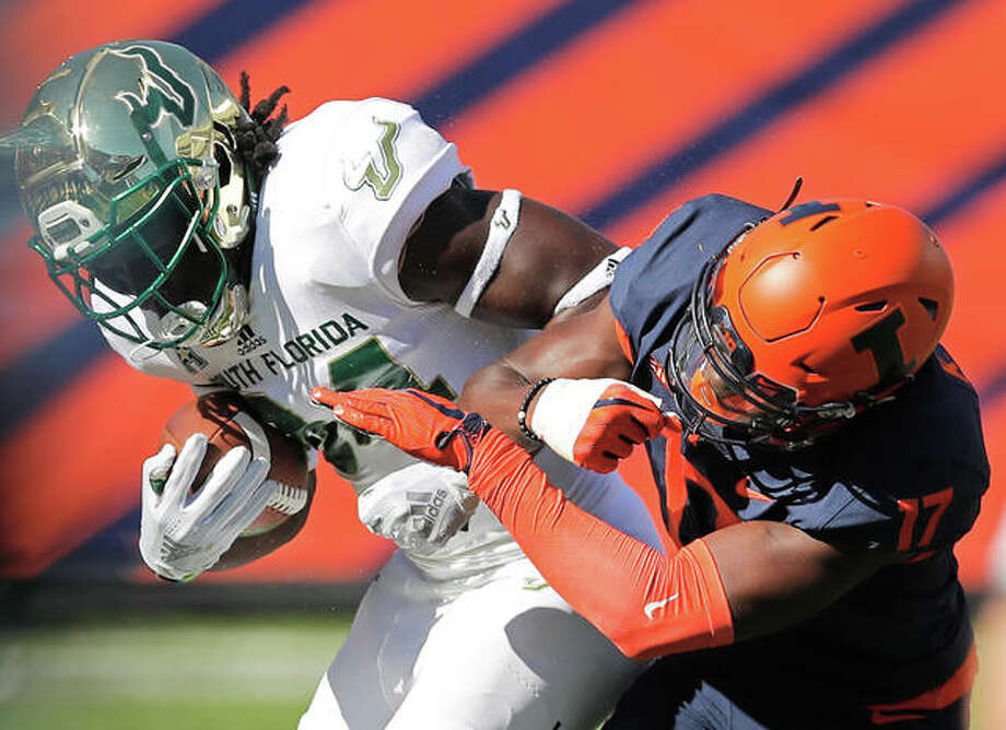 South Florida's Randall St. Felix (left) is tackled by Illinois's Kendall Smith during the first half of their college football game Saturday in Chicago. Photo: Associated Press
