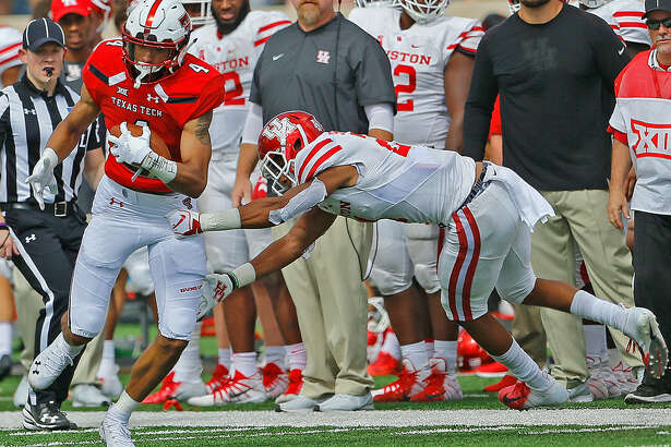 Texas Tech receiver Antoine Wesley (4) pulls away from a Houston defender on his way to a long gain. Photo by Wade H Clay