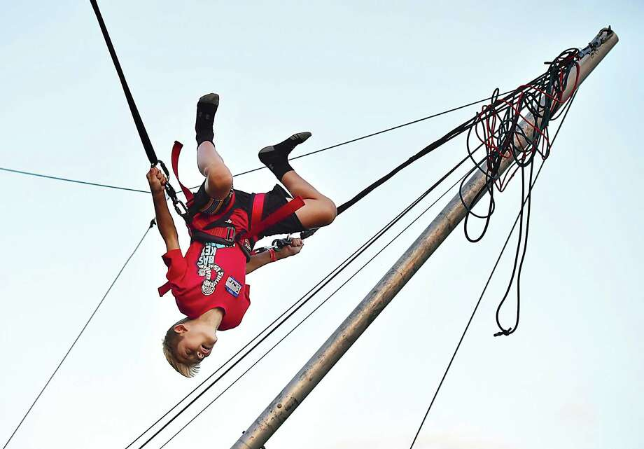 "Emerson Nappi, 10, executes a triple somersault on the Power Jumper at the Orange Country Fair Saturday, September 15, 2018, at the fairgrounds at 525 Orange Center Road in Orange. Emerson said, ""I can do a somersault from just standing on the ground."" Photo: Catherine Avalone, Hearst Connecticut Media / New Haven Register"