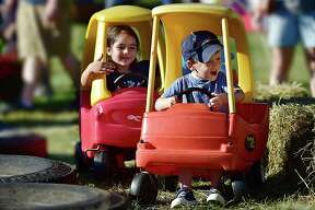 Sean Synnott, 3 and Michelle Imanov, 5, both of Orange get in a traffic jam riding cozy coupes at the Orange Country Fair Saturday, September 15, 2018, at the fairgrounds at 525 Orange Center Road in Orange.