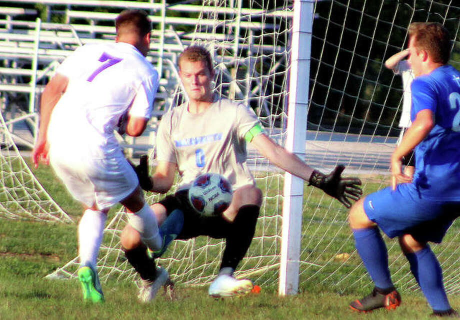 Marquette goalie Nick Hemann makes a save on a shot by Collinsville's Luke Liljegren (7) in the first half of Saturday night's game at Gordon Moore Park. The game ended in a 2-2 tie. At right is Marquette's Nathan Joehl. Photo: Pete Hayes | The Telegraph
