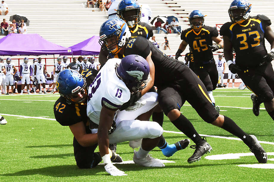Wayland Baptist redshirt junior linebacker Jared Brown (42) and redshirt junior defensive back David Garza (right) combine to tackle Southwester Assemblies of God junior wide receiver Stephon Free (13) during both team's first Sooner Athletic Conference football game of the season on Saturday at Greg Sherwood Memorial Stadium in Plainview. The Lions won, 54-23. Photo: Claudia Lusk/Wayland Baptist University