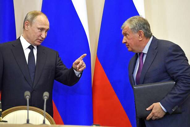 FILE In this file photo taken on Wednesday, May 12, 2018, Russian President Vladimir Putin, left, speaks with Igor Sechin, CEO of Russian oil giant Rosneft, at a joint news conference with Italian Prime Minister Paolo Gentiloni at the Bocharov Ruchei state residence in Russian Black Sea resort of Sochi, Russia. Experts say President Vladimir Putin isn't necessarily dictating every Russian influence campaign abroad. Some accused of meddling in the 2016 U.S. elections appear to be ambitious individuals taking the initiative based on signals from the presidential entourage. (Yuri Kadobnov/ Pool photo via AP, File)