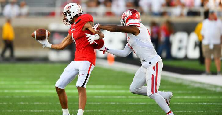 LUBBOCK, TX - SEPTEMBER 15: Antoine Wesley #4 of the Texas Tech Red Raiders juggles the ball but still makes the catch against Nick Watkins #9 of the Houston Cougars during the game on September 15, 2018 at Jones AT&T Stadium in Lubbock, Texas. Texas Tech won the game 63-49. (Photo by John Weast/Getty Images)