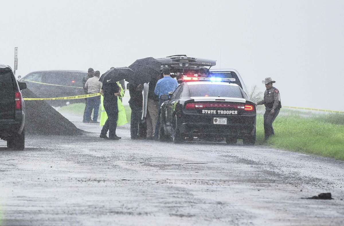 Law enforcement officers investigate the scene where a fourth body was found on Sept. 15, 2018, near Interstate 35 northbound at mile marker 14. Officials say she was the victim of a serial killer and have charged Border Patrol agent Juan David Ortiz with four counts of murder.