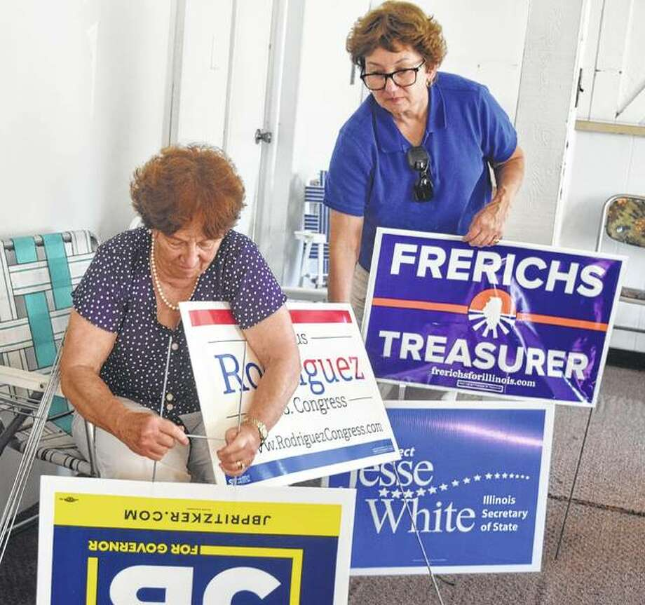Judith Luchenbach Nelson (left), president of the Morgan County Democrats, and Dana Ryan, the Democratic central committee chair of Morgan County, put together signs Saturday during the open house at the Morgan County Democrats' new headquarters. The organization will use the headquarters, located at 252 W. Morton Ave., until Nov. 6 and the office will be open on Tuesdays and Thursdays from 4:30 to 6:30 p.m. and on Saturdays from 10 a.m. to 2 p.m. Photo: Samantha McDaniel-Ogletree | Journal-Courier