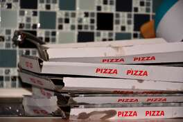 Five empty dirty boxes of pizza lie on the kitchen table.