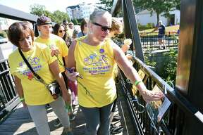 Sue Monroe (center) of Stratford extends a kiss to Dan Macy while crossing the Hotchkiss Bridge at the start of the Folks on Spokes and Step Forward Memorial Walk in Milford on September 16, 2018. The bridge was decorated with a photo tribute to loved ones who died from mental health or substance abuse related issues. The ride and walk raised funds for Bridges Healthcare to support mental health and addiction recovery.