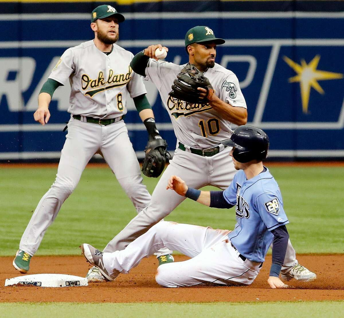 ST. PETERSBURG, FL SEPTEMBER 16: Marcus Semien #10 of the Oakland Athletics throws the ball to first base after tagging second for the force out on Matt Duffy #5 of the Tampa Bay Rays as teammate Jed Lowrie #8 watches during the first inning of the game against the Tampa Bay Rays at Tropicana Field on September 16, 2018 in St. Petersburg, Florida. (Photo by Joseph Garnett Jr./Getty Images)