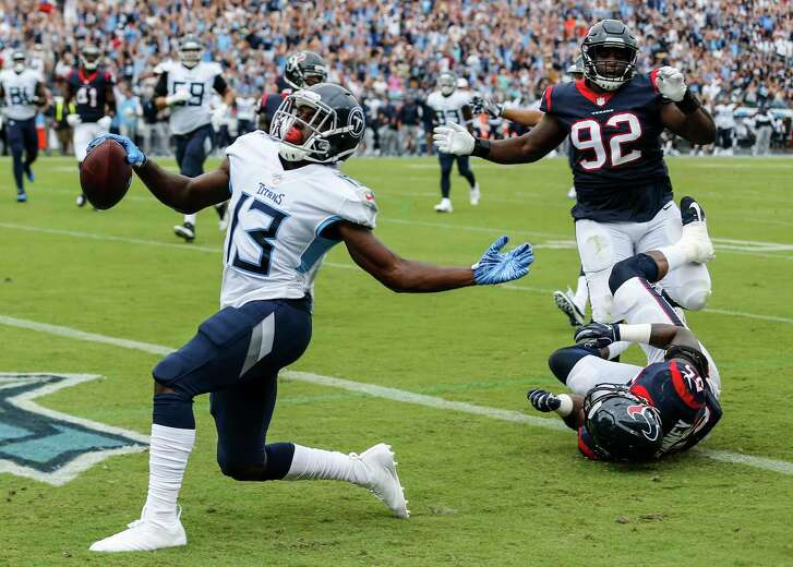 Tennessee Titans wide receiver Taywan Taylor (13) runs past Houston Texans linebacker Benardrick McKinney (55) and defensive tackle Brandon Dunn (92) for an 18-yard touchdown reception during the first quarter of an NFL football game at Nissan Stadium on Sunday, Sept. 16, 2018, in Nashville.