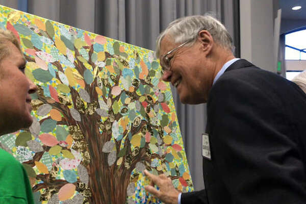 "State Sen. Bill Haine gets a closer look at the ""Tree of Life,"" created by OSF Saint Anthony's Oncology Medical Assistant Tanya McIntosh, during a special celebration of cancer survivorship hosted by OSF HealthCare Saint Anthony's Health Center this week. Haine was one of the many survivors who put his name on a leaf and attached it to the rendering."