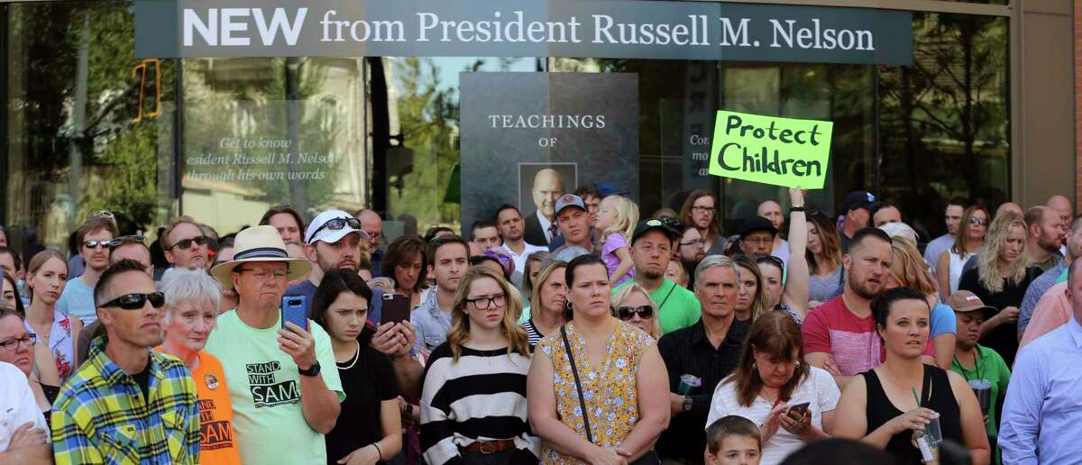 People show their support for Sam Young as he speaks during a press conference Sunday, Sept. 16, 2018, in Salt Lake City. Young, a Mormon man who led a campaign criticizing the church's practice of allowing closed-door, one-on-one interviews of youth by lay leaders has been kicked out of the faith. Young read a verdict letter for the first time Sunday that had been delivered to him following an earlier disciplinary hearing with local church leaders in Houston. (AP Photo/Rick Bowmer)
