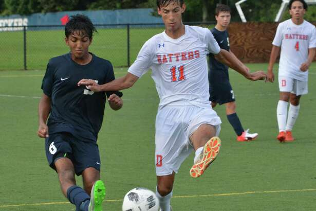 Danbury's Anthony Salinas, right, tries to get the ball from Staples' Surya Balaji during boys soccer action on Wednesday in Westport. Staples is celebrating 60 years as a program in the sport.