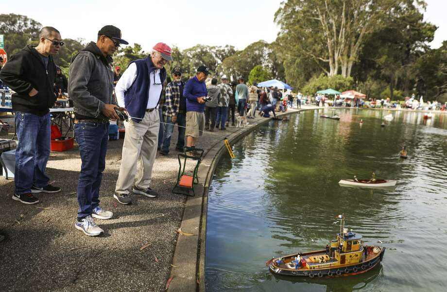 Julio Millare (second from left) controls his boat after lowering it into Spreckels Lake during the Model Boats on Parade event in Golden Gate Park. The event's sponsor, the San Francisco Model Yacht Club, is marking 12 decades of boat-building passion. Photo: Photos By Gabrielle Lurie / The Chronicle / ONLINE_YES