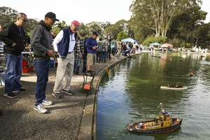 Julio Millare (second from left) controls his boat after lowering it into Spreckels Lake during the Model Boats on Parade event in Golden Gate Park. The event's sponsor, the San Francisco Model Yacht Club, is marking 12 decades of boat-building passion.