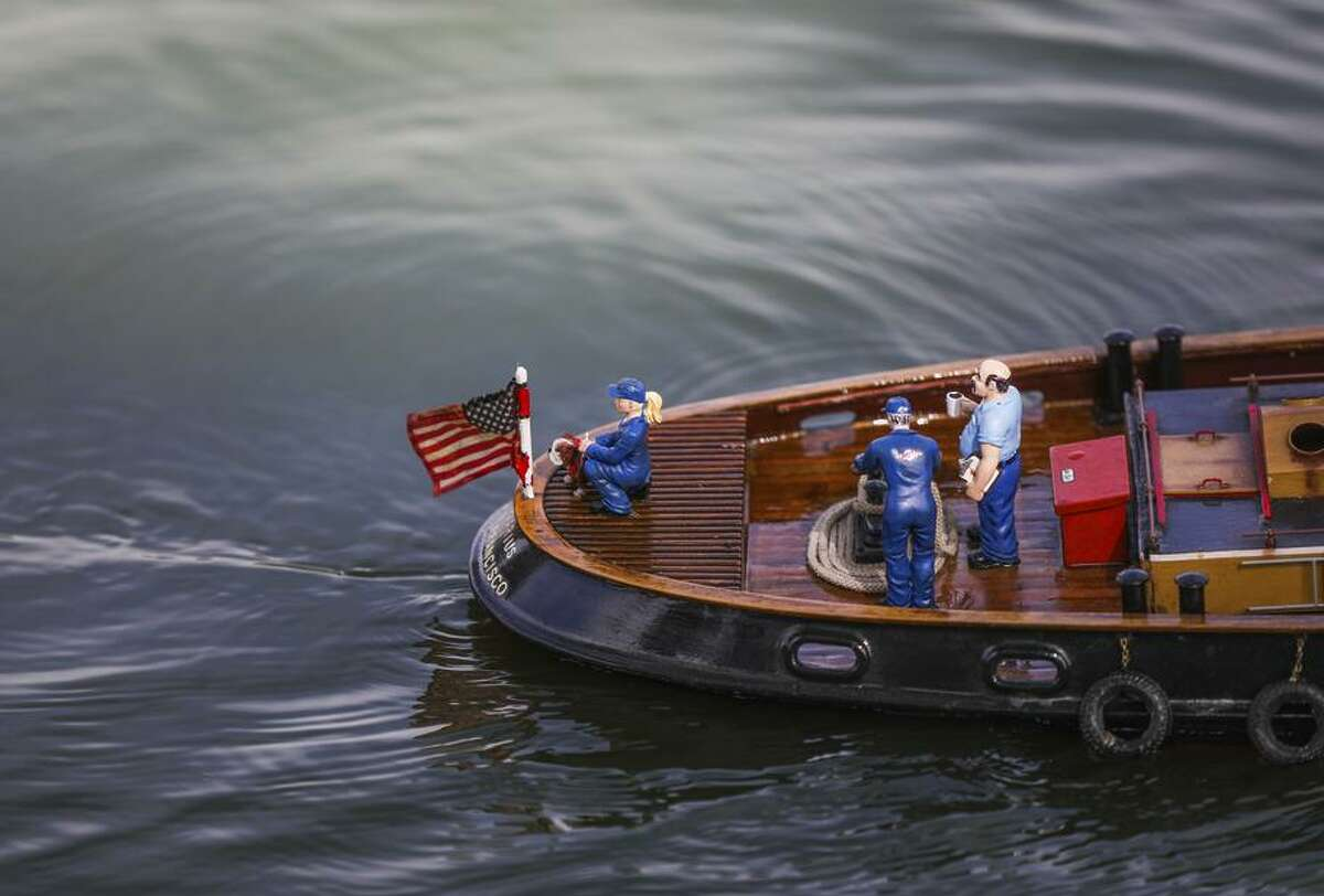 Detailed miniature watercraft glide through Spreckels Lake during the Model Boats on Parade event in the park.
