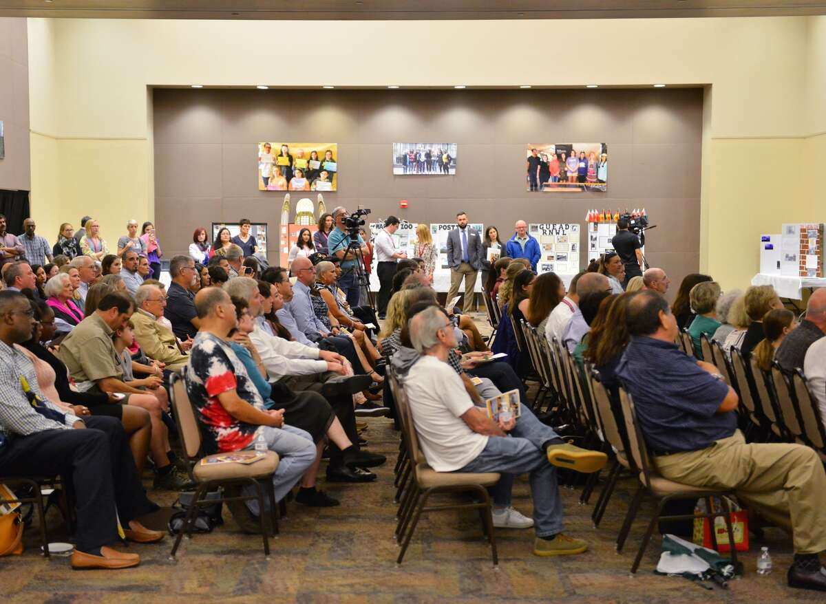 A crowd fills a room in the Campus of the San Antonio Jewish Community Sunday afternoon to hear remarks about the Holocaust Study Seminar that took 12 high school students on a European trip to explore the Holocaust sites. The students then made visual representations of their journey and experiences which were on display.