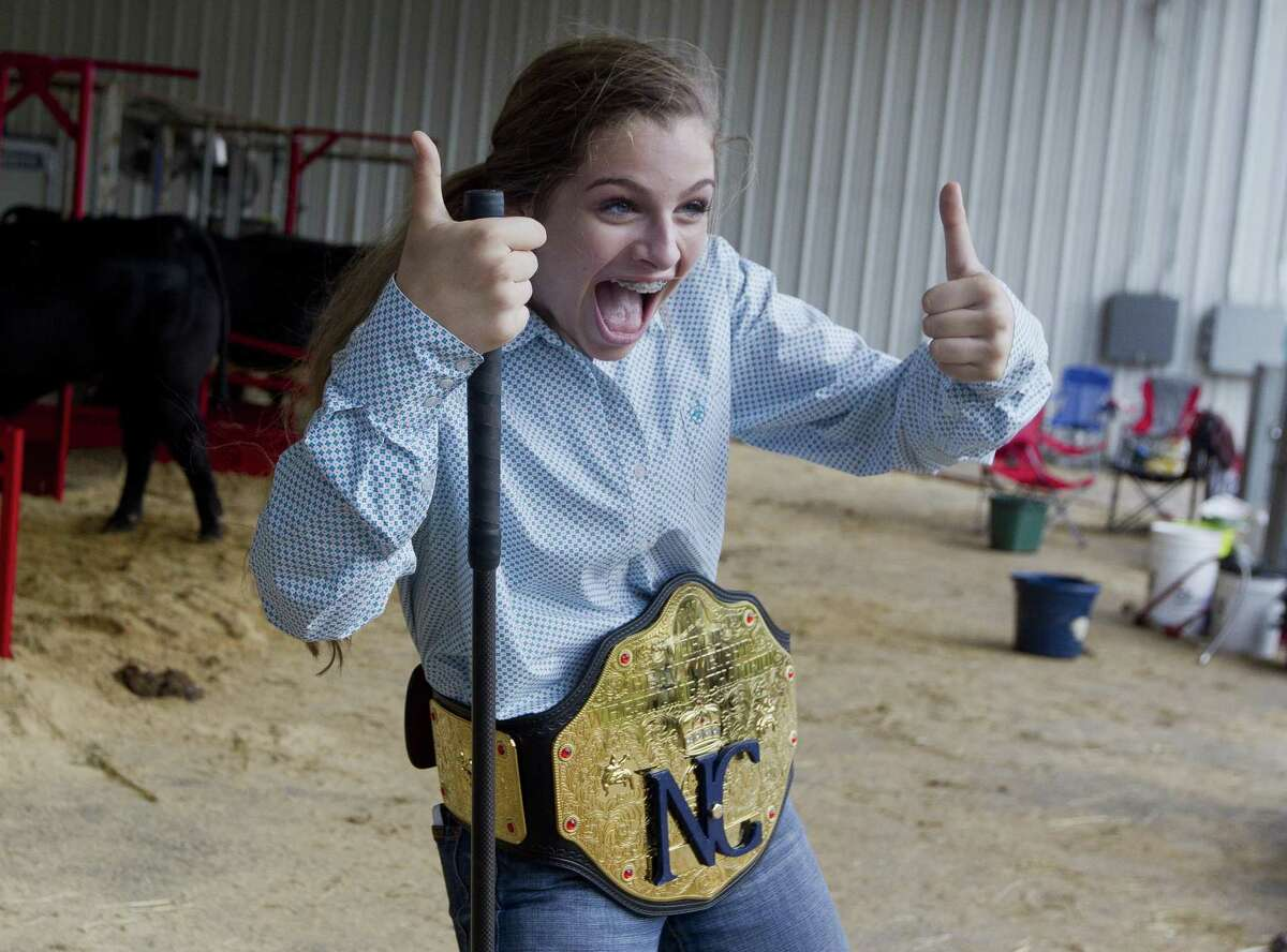 Shelbi Loving of New Caney FFA laughs as she wears the New Caney championship belt after her steer was named grand champion during the East Montgomery County Fair auction at A.V. 'Bull' Sallas Park, Saturday, Friday, Sept. 15, 2018, in New Caney.