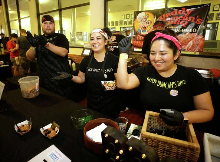 Chef Randy Duncan, left, Sylva Duncan, and Jessica Gonzalez, right, with Daddy Duncan's BBQ cheer as someone places a voting token into their ballot box for the people's choice award during Houston BBQ Throwdown at Saint Arnold Brewing Company, 2000 Lyons Ave., Sunday, Sept. 16, 2018, in Houston.