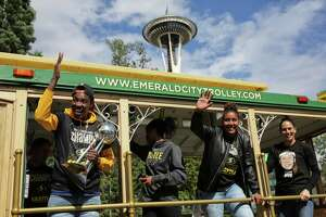 Seattle Storm players (from left) Natasha Howard. Jordin Canada, Kaleena Mosqueda-Lewis and Sue Bird wave at fans from the trolley during a parade to celebrate the Storm winning the 2018 WNBA basketball championship, Sunday, Sept. 16, 2018, in Seattle.