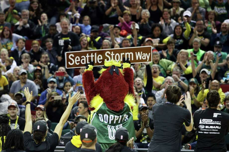 A street sign that will rename a street outside KeyArena is held up by Storm mascot Doppler during a rally at KeyArena to celebrate the Storm winning the 2018 WNBA basketball championship, Sunday, Sept. 16, 2018, in Seattle. Photo: GENNA MARTIN, SEATTLEPI.COM / SEATTLEPI.COM