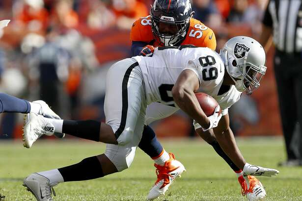 Denver Broncos linebacker Von Miller (58) hits Oakland Raiders wide receiver Amari Cooper (89) during the second half of an NFL football game, Sunday, Sept. 16, 2018, in Denver. (AP Photo/Jack Dempsey)