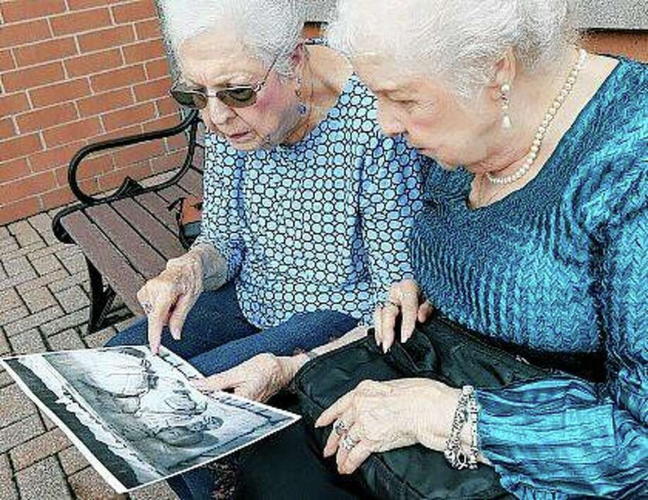 """Jean Harrison of Algonquin (left) and Jane Umbarger of McHenry, known as the """"incubator twins,"""" look at a photo of their infancy as they talk about their experiences. The twin sisters, both 84, were among hundreds of premature infants placed in incubators at the Century of Progress expo in Chicago in 1933 and 1934. They also had a double wedding in 1953, which drew national attention. Photo: Matthew Apgar 