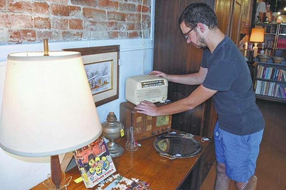 Nick Little of Jacksonville adjusts an old radio in his family's new antiques store in downtown Jacksonville. Photo: Greg Olson | Journal-Courier