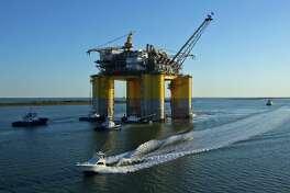 Tug boats transport a Hess Corp. oil platform near Ingleside, Texas, on May 5, 2017.