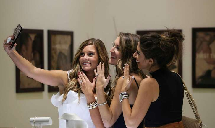 Kylee Angel, from left, Shelbi Adams and Dede Raad take a photograph with jewelries for social media pose for a photograph at the Evening of Design event at Robbins Brothers Jewelry on Wednesday, Sept. 12, 2018, in Houston.