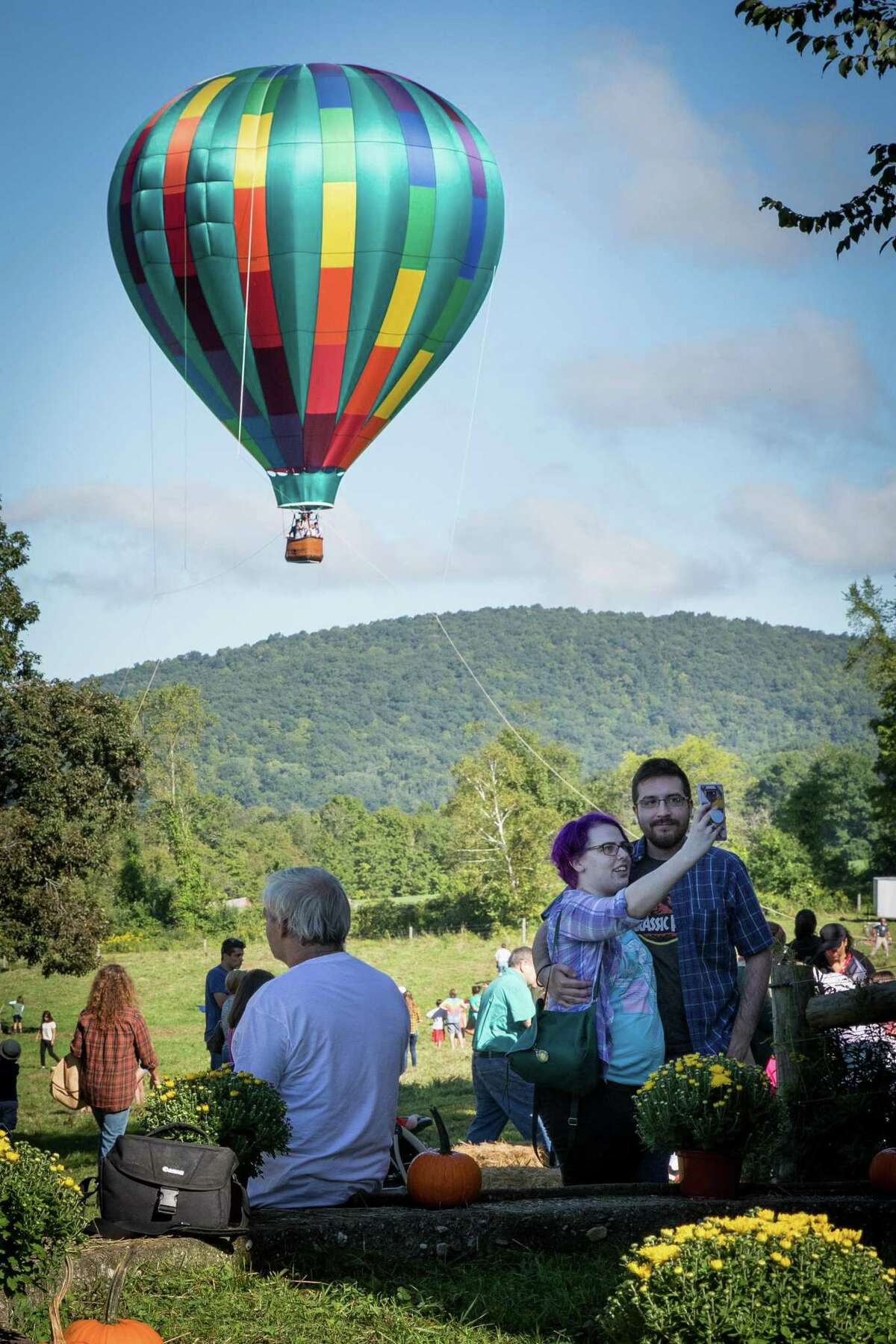 Elizabeth Edwards and Javier Martinez of New Milford pose for a selfie with the hot-air balloon as the background during the Weantinoge Heritage Land Trust fall celebration on Saturday, September 15, 2018, at Smyrski Farm in New Milford, CT. Liberty Balloon Company out of Groveland, NY, gave tethered hot-air balloon rides starting at 8am.
