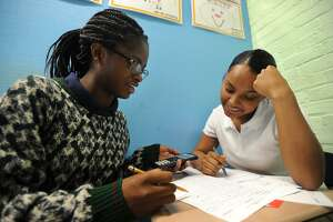 Seniors Christine Menard, left, and Deborah Davidson, both 17 of Bridgeport, work together during pre-calculus class at The Bridge Academy charter school in Bridgeport, Conn. on Wednesday, September 12, 2018. The school has experienced a drop in enrollment which may be due to the opening of the new Harding High School this fall.