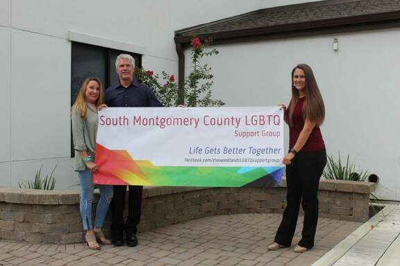 Kirsten Beckler and her husband Phil hold the South Montgomery County LGBTQ Support Group banner with Roxy Waguespack in front of the Lord of Life Lutheran Church.