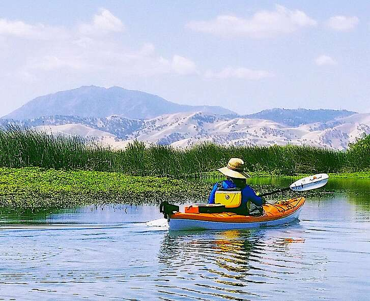 A kayaker paddles along the shore of Sherman Lake, near where the San Joaquin and Sacramento Rivers merge in the Delta, with a silhouette of Mount Diablo on the horizon